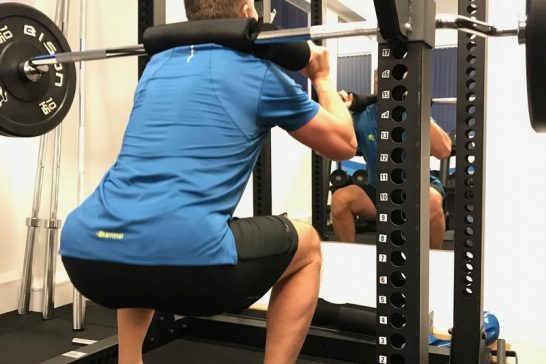 Client performing a safety bar squat