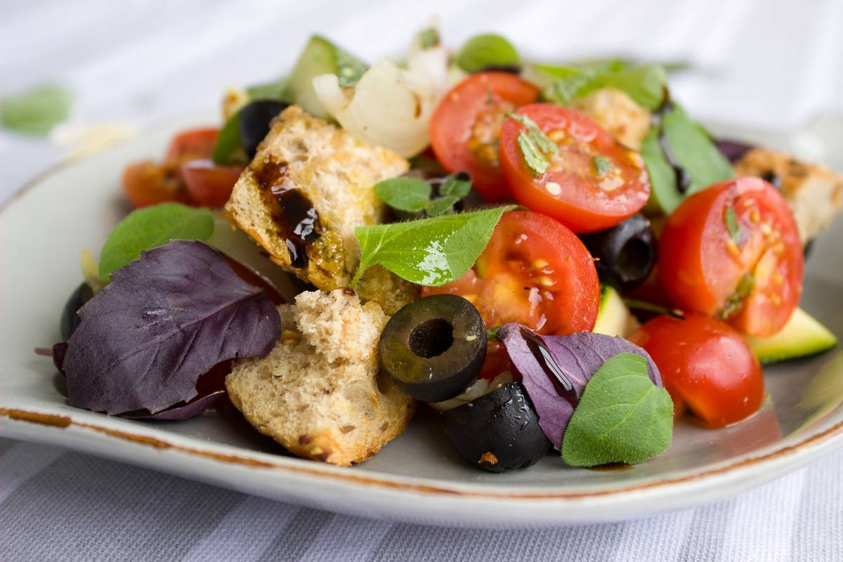 Salad of tomatoes, bread, olives and leaves. Veganism pros and cons