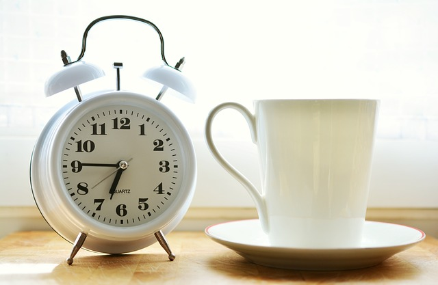 A picture of a white alarm clock next to a cup of coffee
