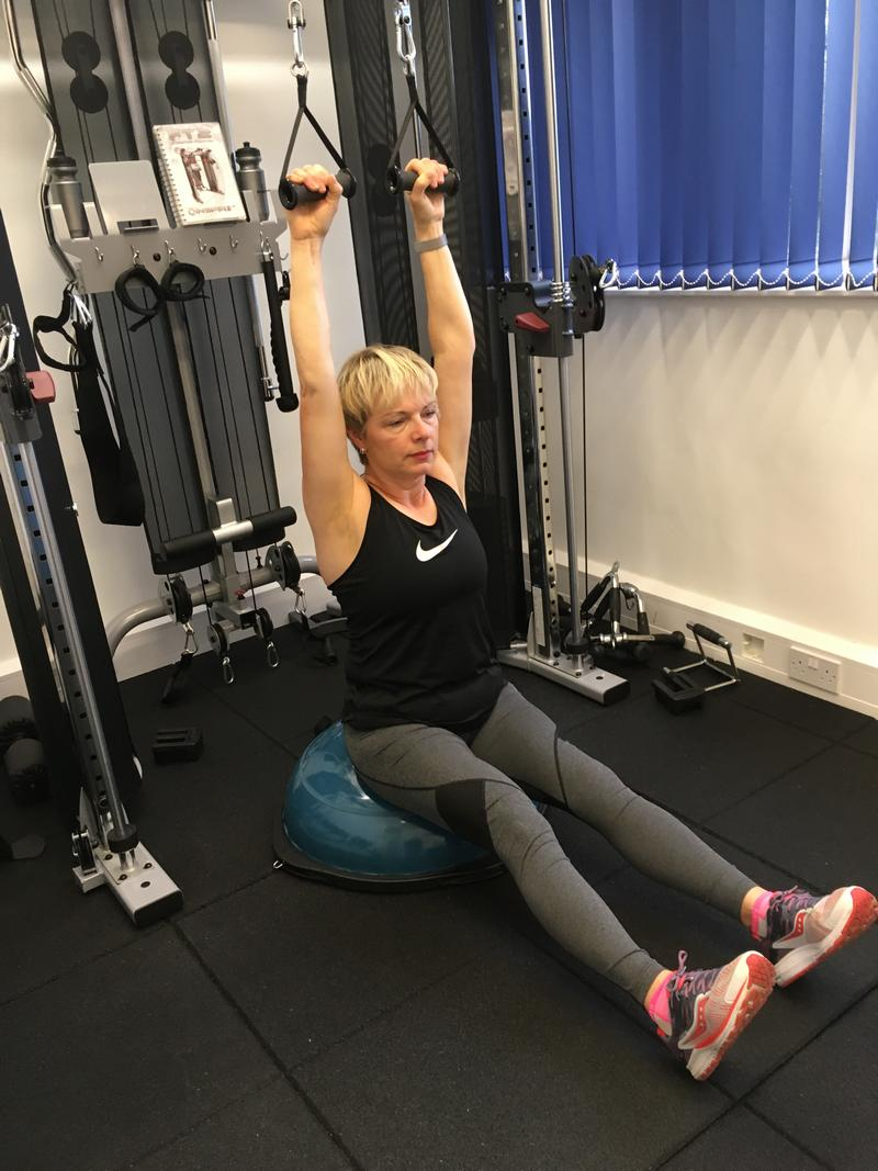 A lady doing resistance training. Performing lat pulldown Weight training will transform you.