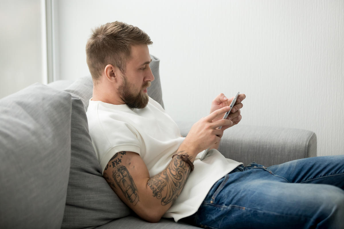 Man slouching on a sofa, seemingly unaware of the health risks of sitting