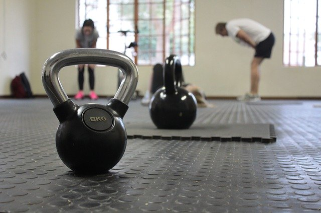 image of exercise equipment with exhausted people in background