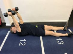 At home upper body workout. Coach doing lying triceps extensions