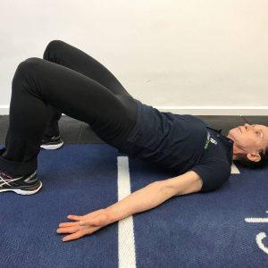 Posture workout - basic. Coach performing hip bridges