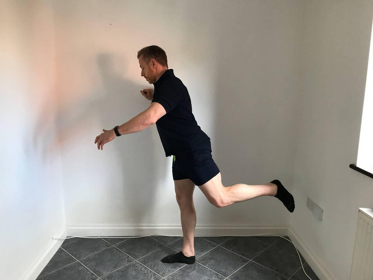 Trainer performing hip swings