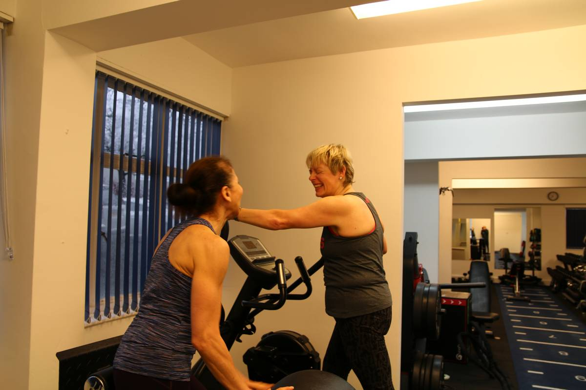 Client warming up on a cross trainer whilst talking to the coach. Top 10 tips for mature lifters