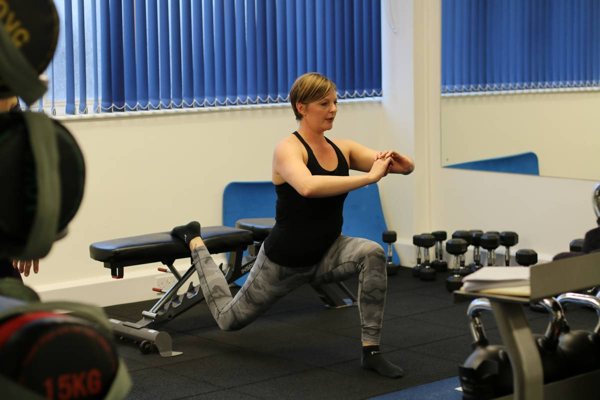 Female client using a single leg exercise rather than doing squats. Top 10 tips for mature lifters