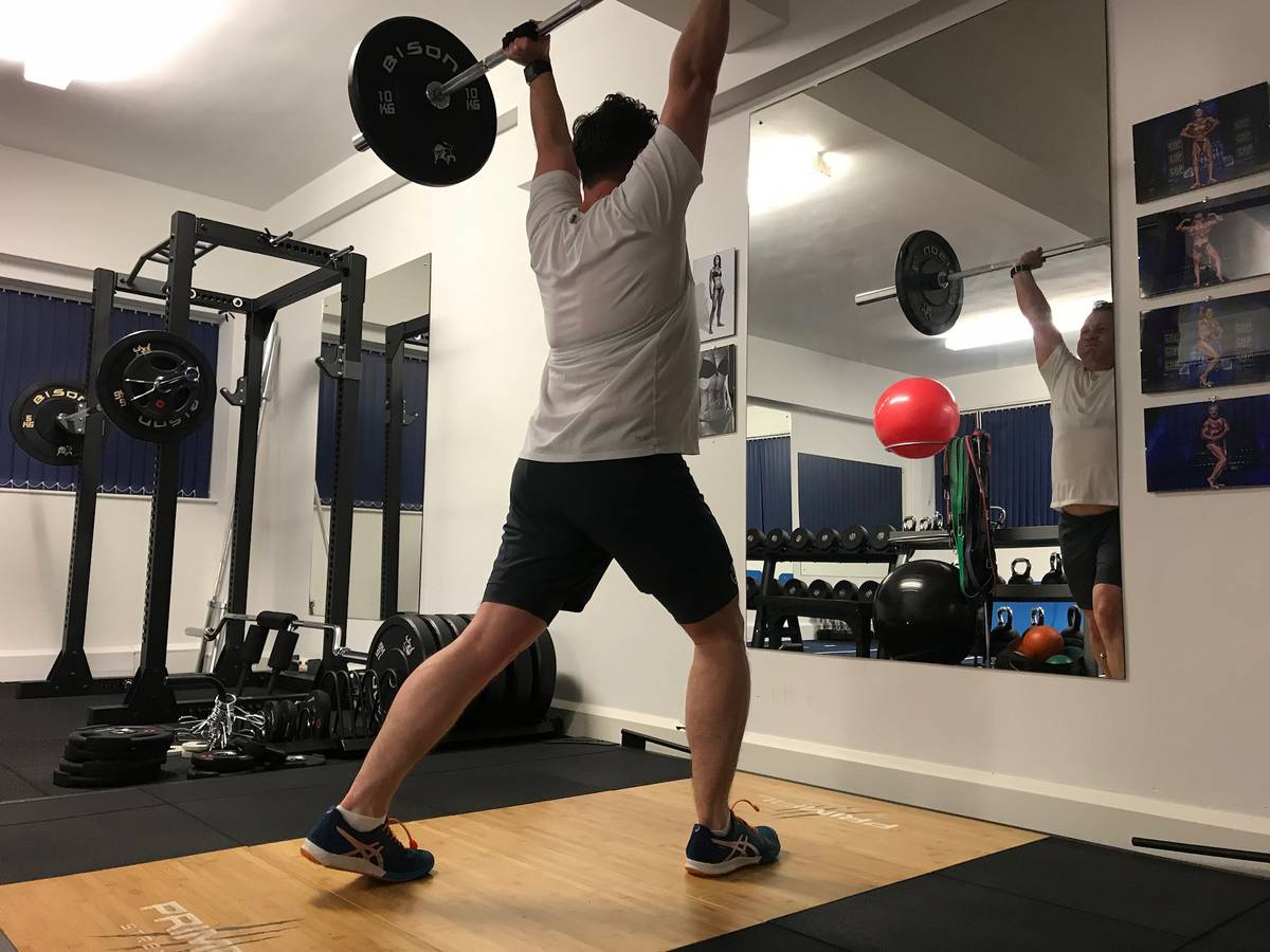 Client doing compound movement, clean and press. Top 10 tips for mature lifters