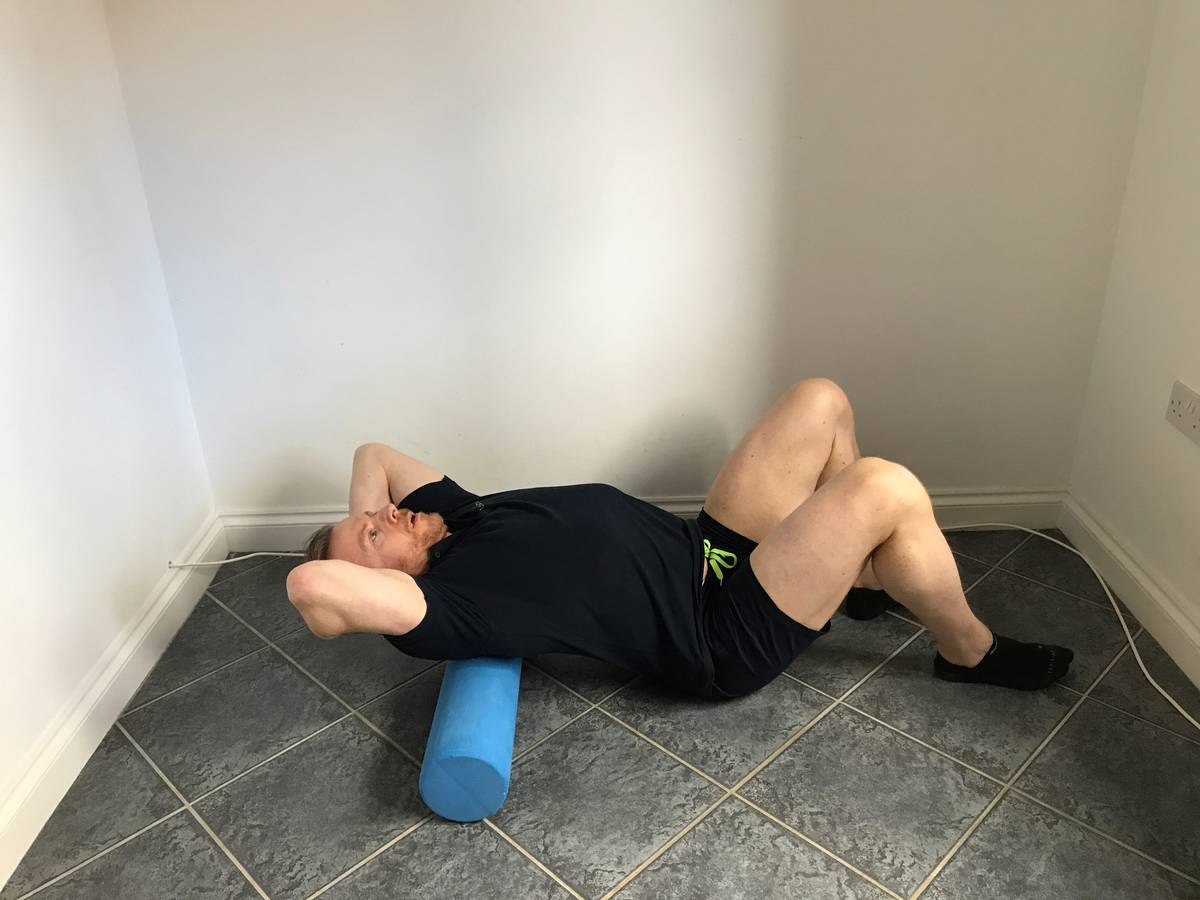 Trainer performing upper back rolling