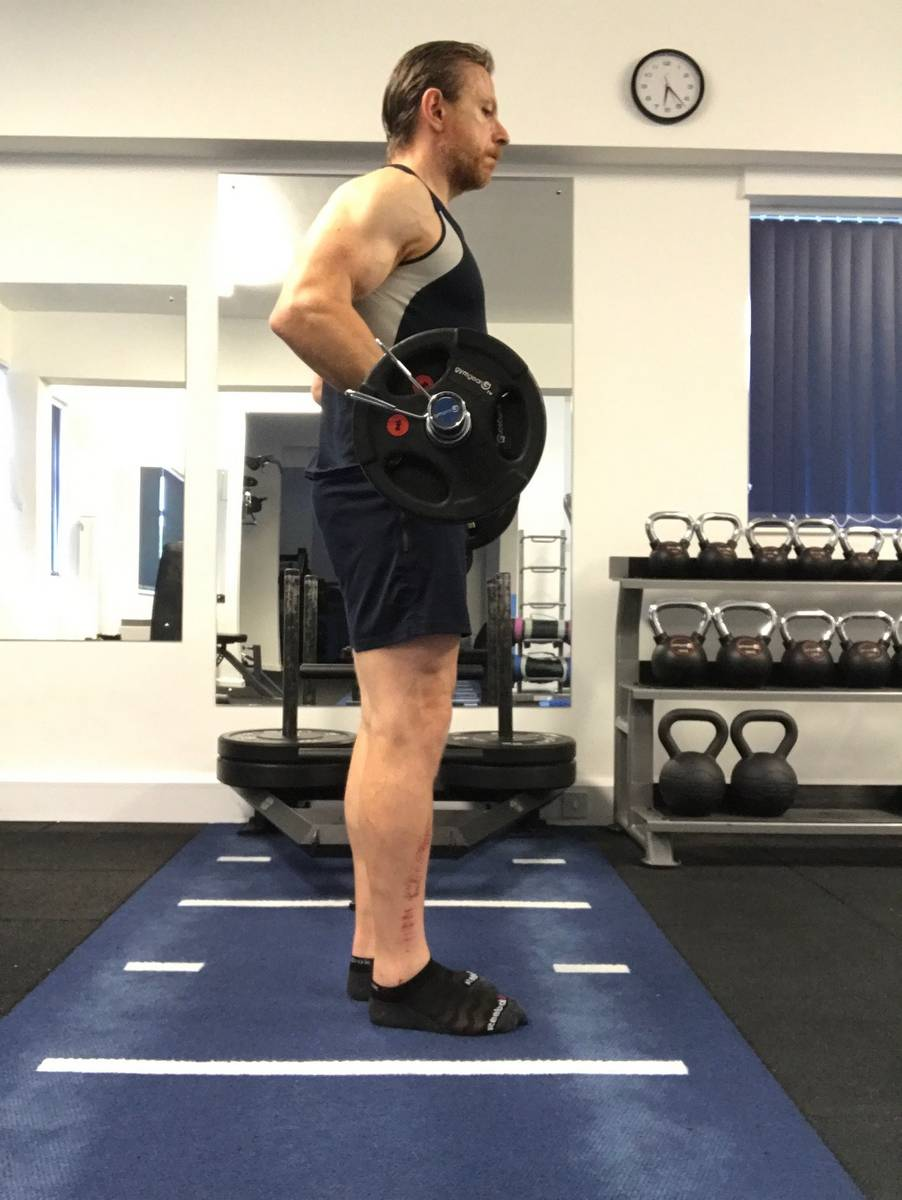Allowing the elbows to fall back in the standing biceps curl takes the load off the biceps