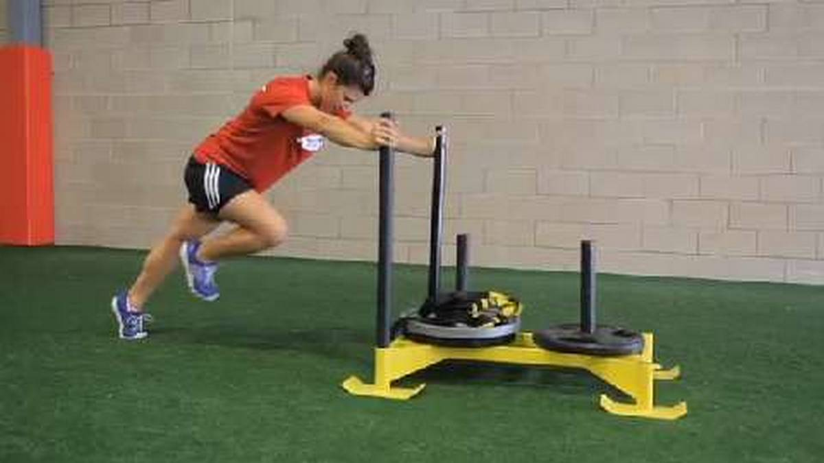 Woman pushing a sled in a gym. Eight reasons why you're not losing weight.