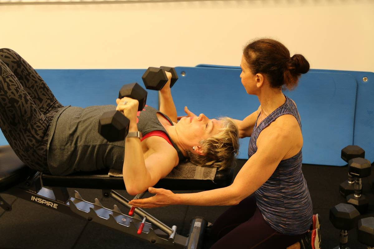 Woman being spotted on dumbbell bench press