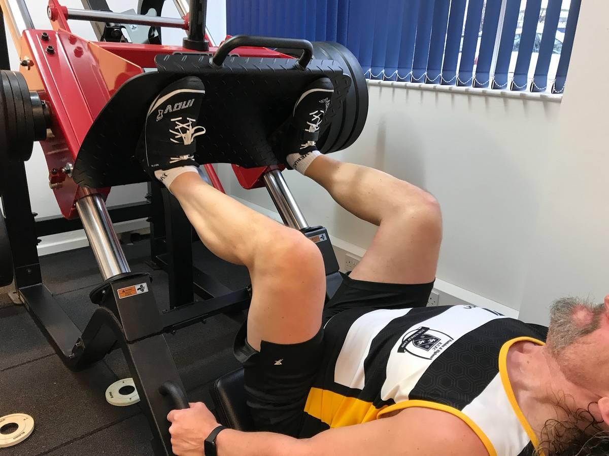 Legs of a man doing leg press