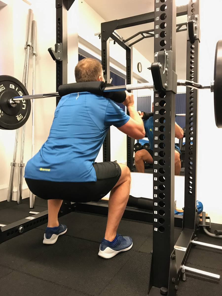 Rear view of a man squatting using a safety bar. How should I train to build muscle