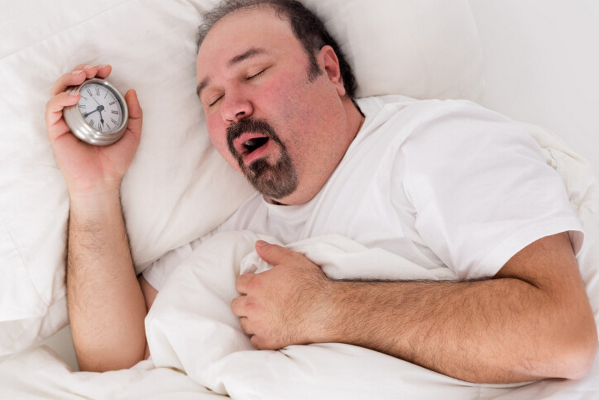 Tired overweight man clutching a clock. Your body clock and weight gain.