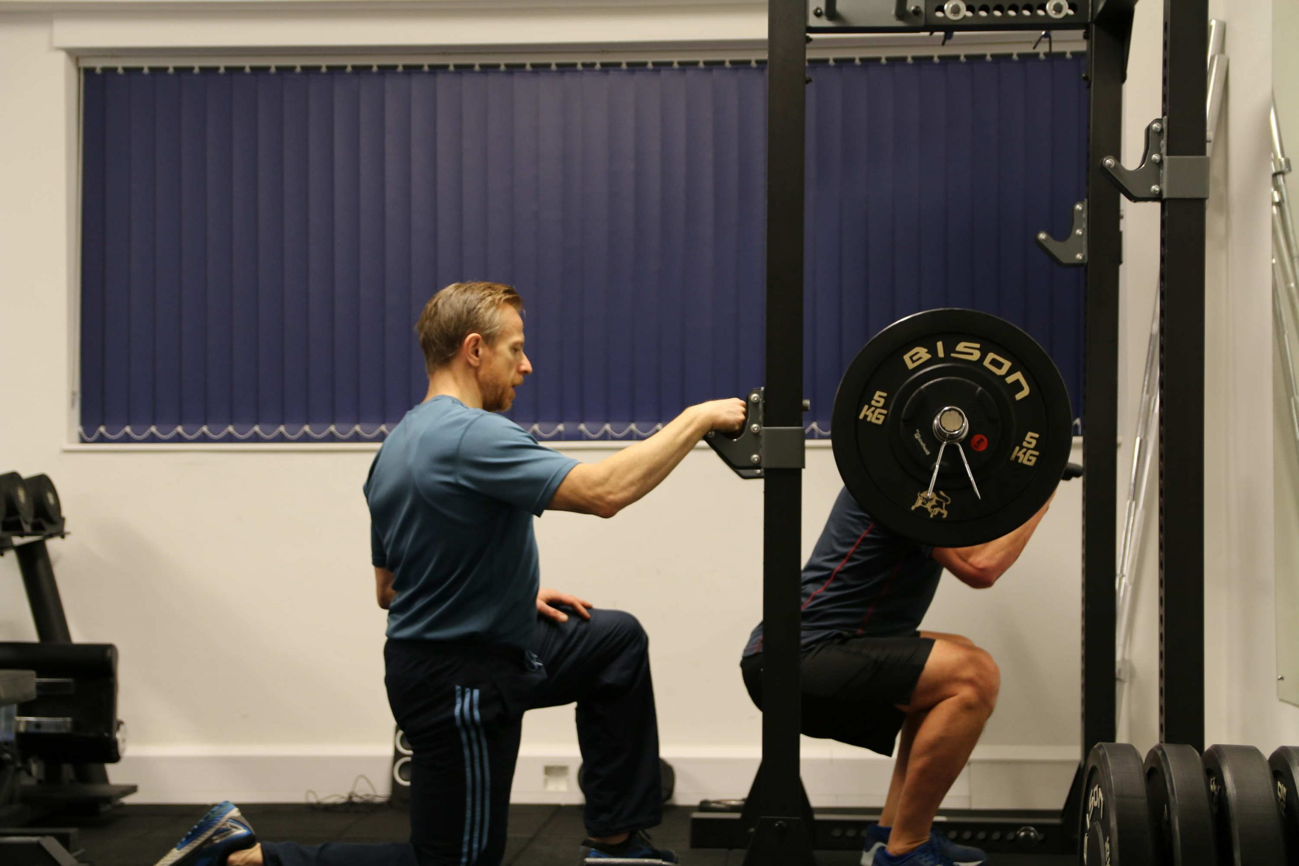 A PT with a client squatting. one reason why use personal training