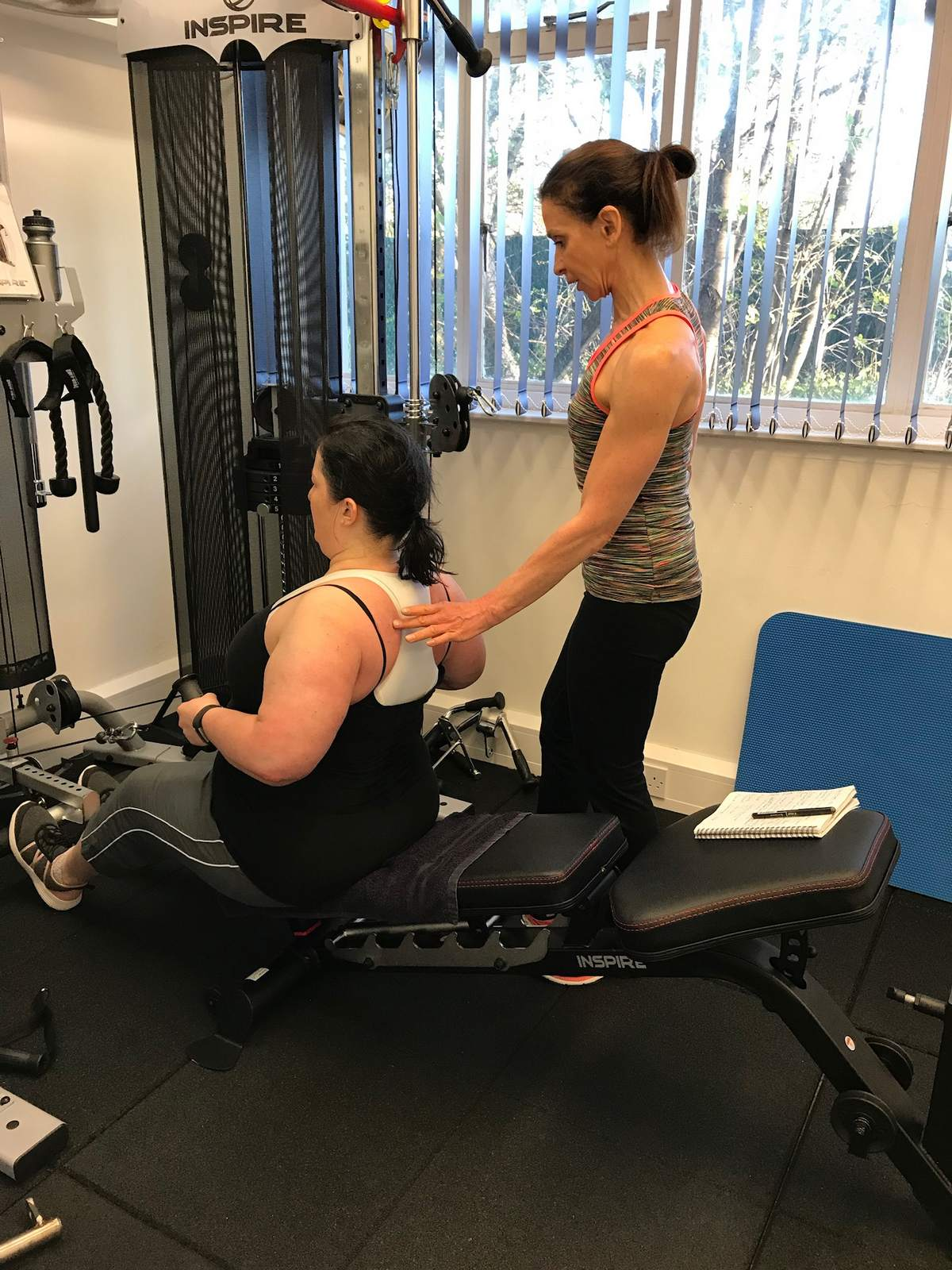 A PT teaching a client how to do cable rows