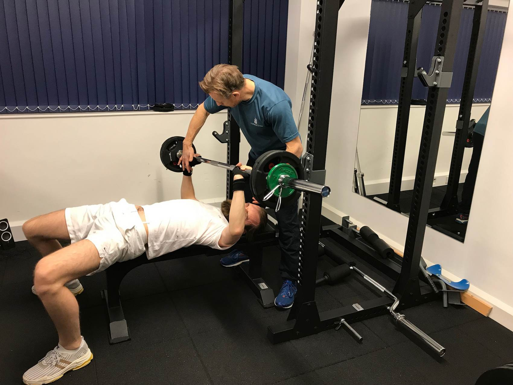 A PT with a client bench pressing.