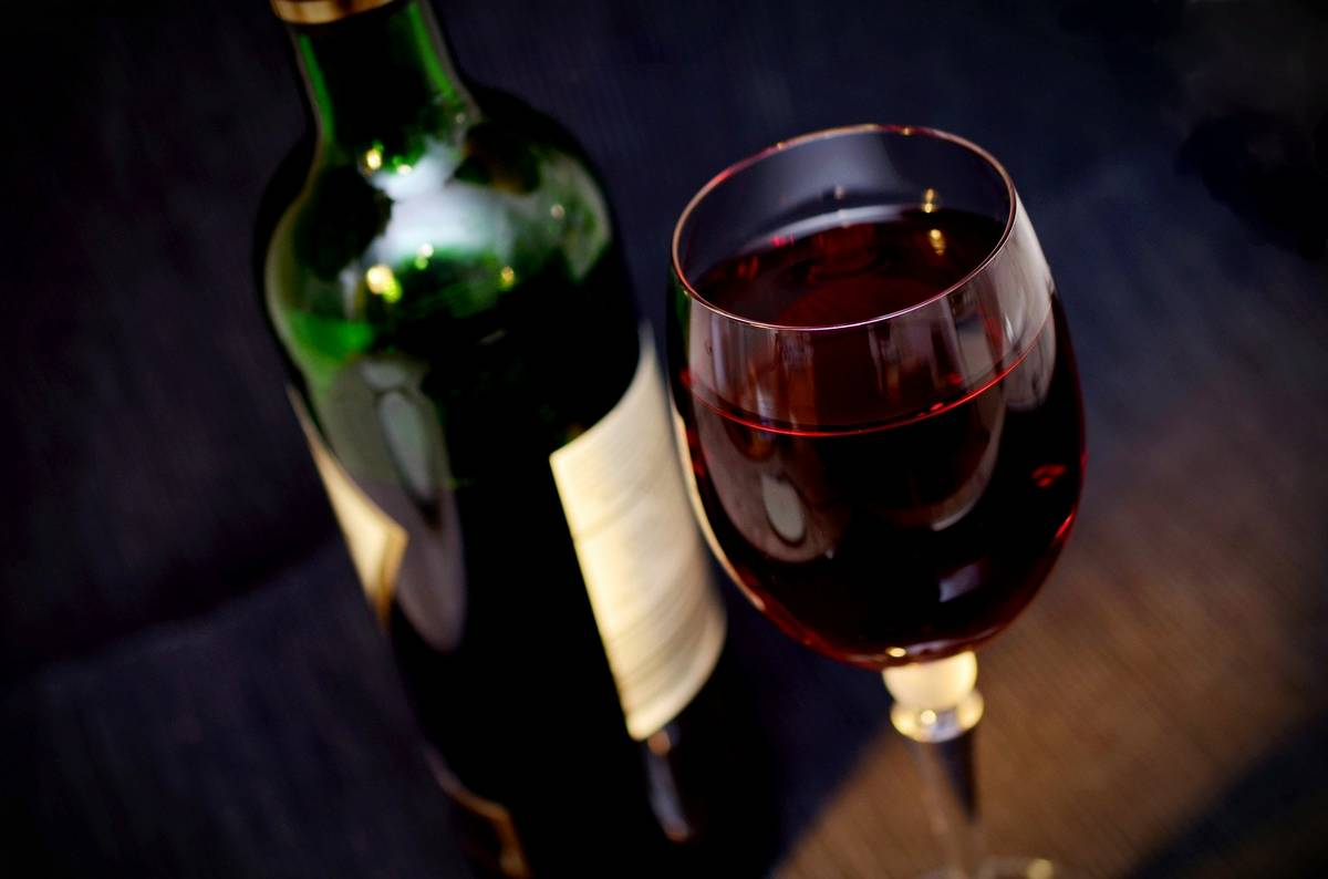 A large glass of red wine next to a part empty bottle. Can you still have a drink and lose weight?