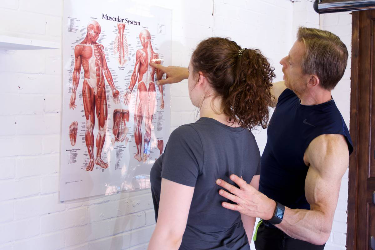 Trainer explaining good posture to a client.