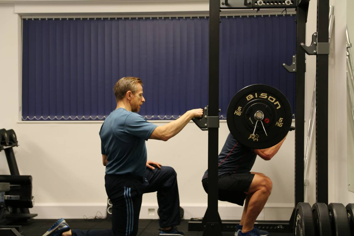 Man performing squats watched by coach.