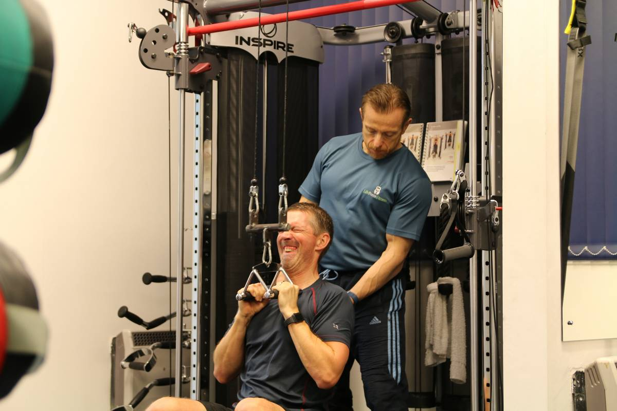 Client performing high intensity exercise: weight training. A personal trainer's guide to losing weight.