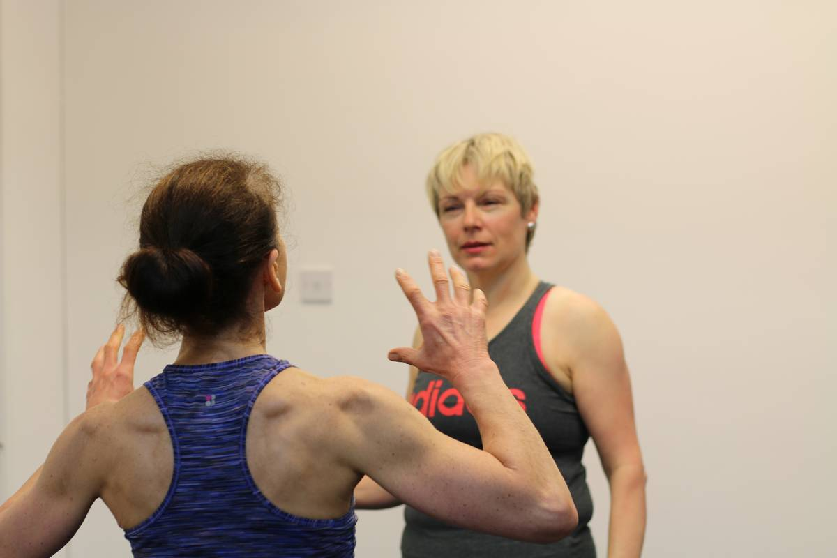 A personal trainer and client in discussion. Personal Trainer's guide to losing weight