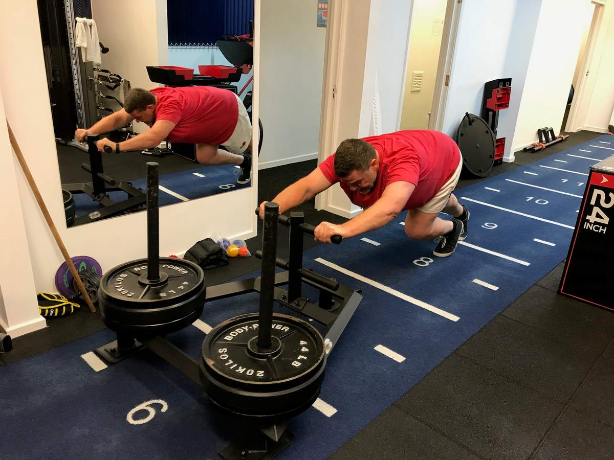 Heavy sled pushes. Private personal training studio.