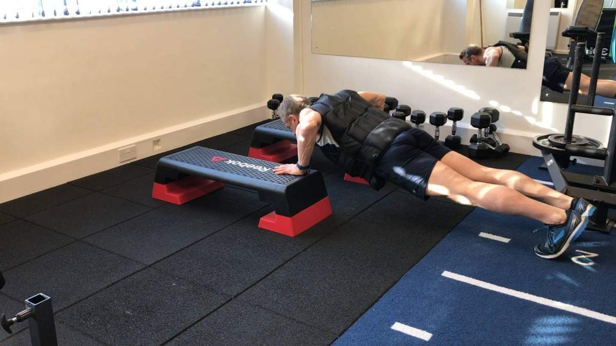 Push ups with weighted vest. Private personal training studio.
