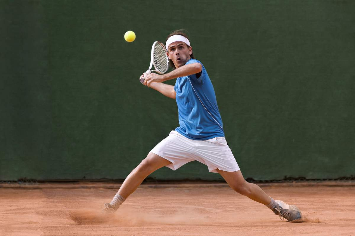 Man playing tennis about to stroke the ball. Good nutrition for sport is essential.