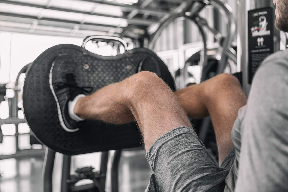 Man performing a leg press exercise. Training is a critical part of eating to build muscle