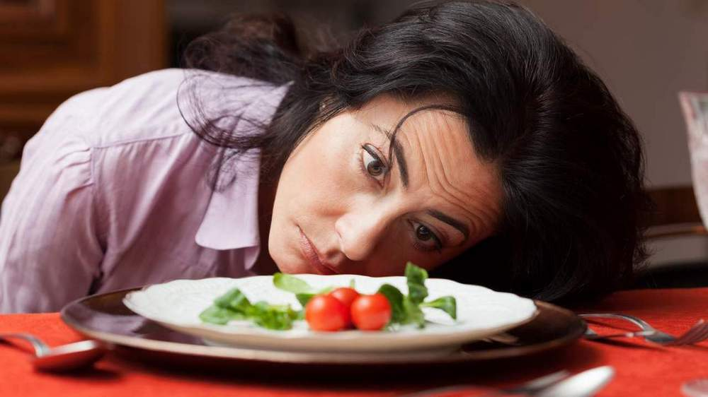 Woman despairingly staring at small plate of food.