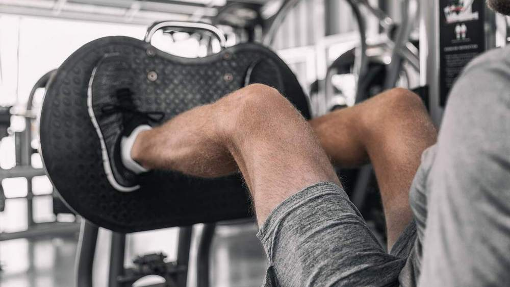 Man performing leg press - legs only. Lifting weights is essential for optimal body composition change.
