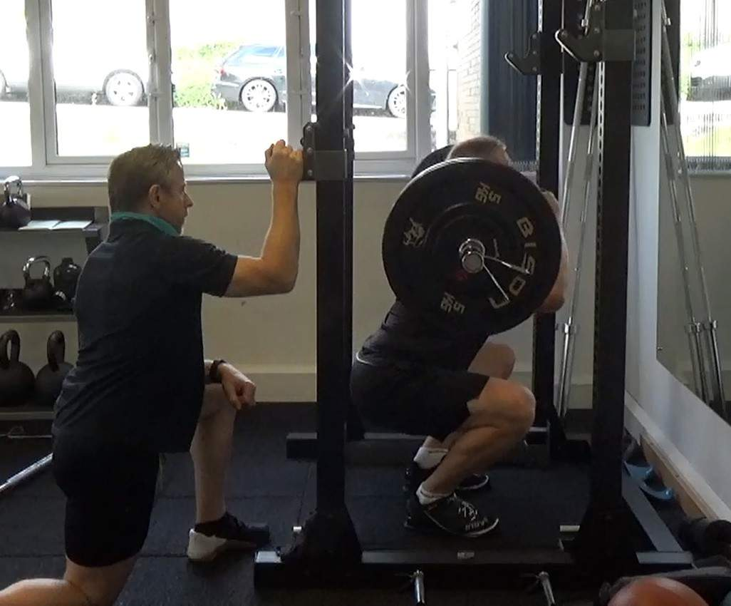 Man doing squats with great form. Resistance training is a great way to combat energy compensation