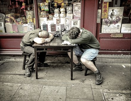 Two men looking very weary slumped over a table. Energy compensation can take the form of reductions in NEAT